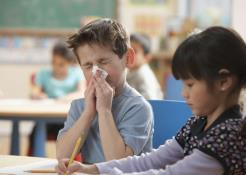 Child blowing nose in classroom