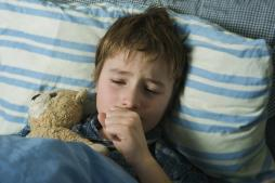 Child with a cough holding a bear.