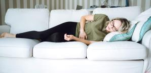 A woman with abdominal pain on her couch